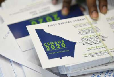 FILE - In this Aug. 13, 2019, file photo a worker gets ready to pass out instructions in how fill out the 2020 census during a town hall meeting in Lithonia, Ga. The U.S. Census Bureau says a test for the 2020 census shows having a question about citizenship didn't have much of an impact on response rates for the general population, though responses by Hispanics were down slightly. The test results were released Thursday, Oct. 31, 2019. (AP Photo/John Amis, File)