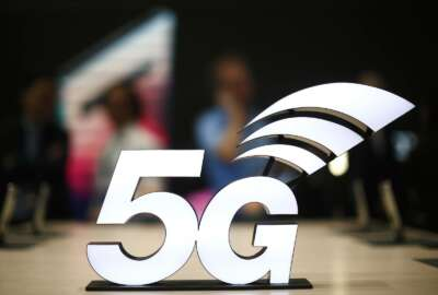 FILE - This Feb. 25, 2019 file photo shows a banner of the 5G network is displayed during the Mobile World Congress wireless show, in Barcelona, Spain.  The U.S. communications regulator will hold a massive auction to bolster 5G service, the next generation of mobile networks, and will spend $20 billion for rural internet.  5G will mean faster wireless speeds and has implications for technologies like self-driving cars and augmented reality.   The Federal Communications Commission said Friday, April 12,  that it would hold the largest auction in U.S. history, of 3,400 megahertz, to boost wireless companies' networks.  (AP Photo/Manu Fernandez, File)