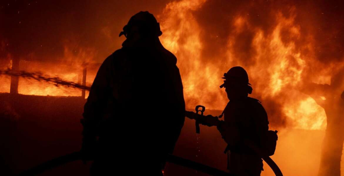 Firefighters try to save a home on Tigertail Road during the Getty fire, Monday, Oct. 28, 2019, in Los Angeles, Calif. (AP Photo/Christian Monterrosa)