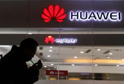 FILE - In this Dec. 6, 2018, file photo, a man lights a cigarette outside a Huawei retail shop in Beijing.  The Federal Communications Commission on Friday, Nov. 22, 2019 voted, 5-0, to bar U.S. telecommunications providers from using government subsidies to pay for networking equipment from companies that are a threat to national security. The agency says China's Huawei and ZTE pose such a threat.  (AP Photo/Ng Han Guan, File)