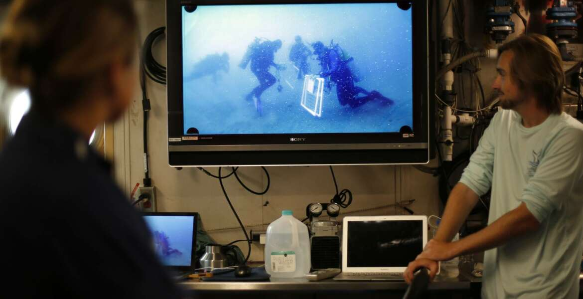 Researchers and crew aboard the NOAA Ship Nancy Foster watch footage of divers working at Gray's Reef, about 20 miles off the coast of Georgia on Wednesday, Aug. 4, 2019. (AP Photo/Robert F. Bukaty)