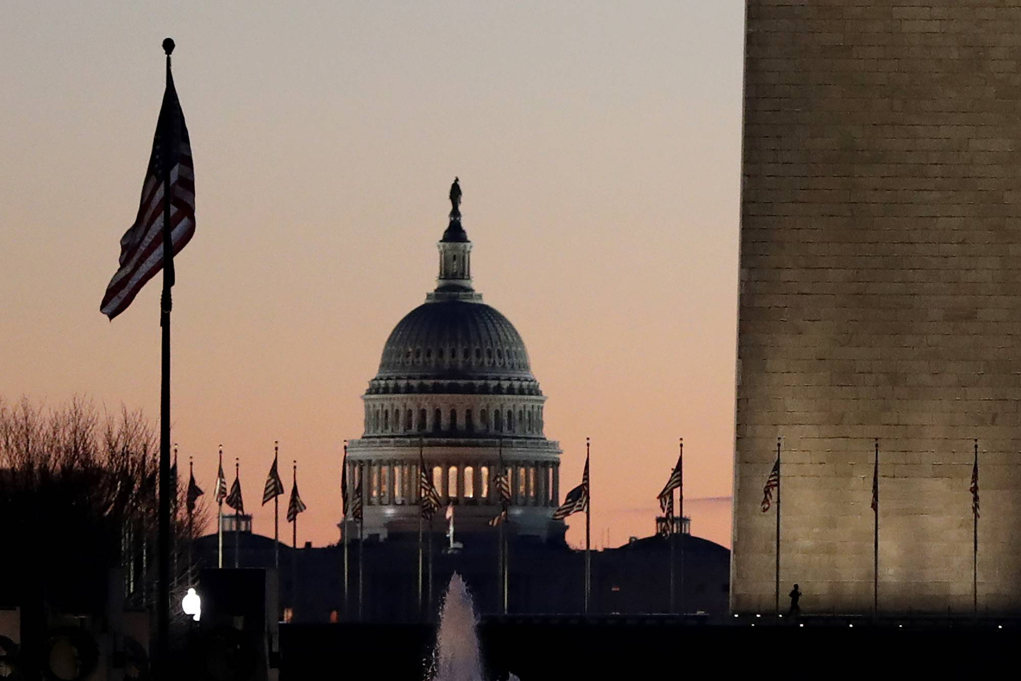 The U.S. Capitol building, center, and part of the Washington Monument, right, are seen at sunrise, Wednesday, Dec. 18, 2019, on Capitol Hill in Washington. President Donald Trump is on the cusp of being impeached by the House, with a historic debate set Wednesday on charges that he abused his power and obstructed Congress ahead of votes that will leave a defining mark on his tenure at the White House. (AP Photo/Julio Cortez)