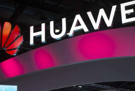 In this Oct. 31, 2019, photo, attendees walk past a display for 5G services from Chinese technology firm Huawei at the PT Expo in Beijing. Chinese tech giant Huawei is asking a U.S. federal court to throw out a rule that bars rural phone carriers from using government money to purchase its equipment on security grounds, announced Thursday, Dec. 5, 2019. (AP Photo/Mark Schiefelbein)