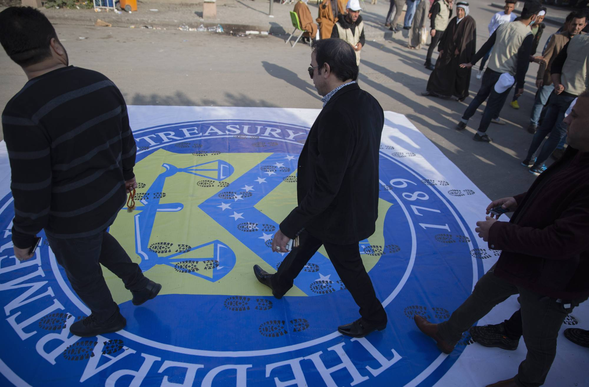 Iraqi protesters walk over a big poster with the logo of the US Department Of The Treasury, that was spread on the street by the organizers to show disrespect, during a rally for the Shiite group Asaib Ahl al-Haq, in Baghdad, Iraq, Saturday, Dec. 14, 2019.   (AP Photo/Nasser Nasser)