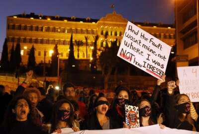 Protesters chant placards during a demonstration to protest sexual harassment and bullying and demanding rights, in front of the government house in downtown Beirut, Lebanon, Saturday, Dec. 7, 2019. Scores of women marched through the streets to protest sexual harassment and bullying and demanding rights including the passing of citizenship to children of Lebanese women married to foreigners. (AP Photo/Bilal Hussein)