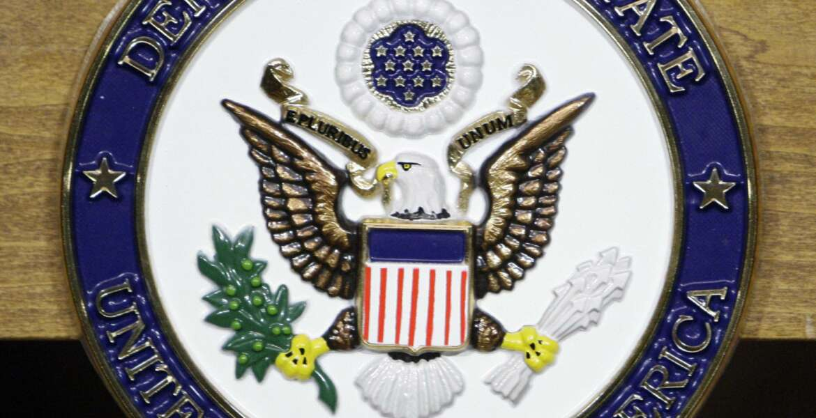 FILE - This Jan. 25, 2010, file photo, shows the United States Department of State seal on a podium at the State Department in Washington.  Two organizations of documentary filmmakers filed a federal lawsuit Thursday arguing that new rules requiring U.S. visa applicants to register their social media handles are making them fearful of publicly speaking their minds.  State Department rules took effect in May and apply to more than 14 million applicants each year, requiring them to register all their social media handles from the past five years on about 20 different online platforms. (AP Photo/Alex Brandon, File)