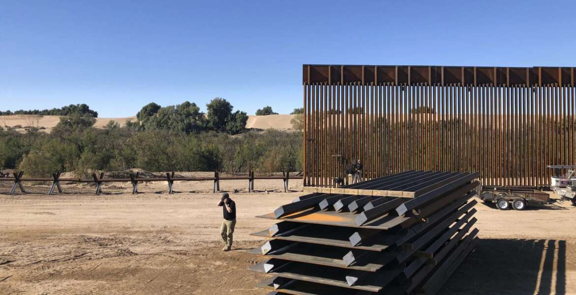 In this Jan. 10, 2020, photo, people work at a portion of border wall which is under construction in Yuma, Ariz. Illegal border crossings have plummeted as the Trump administration has extended a policy to make asylum seekers wait in Mexico for court hearings in the U.S. (AP Photo/Elliot Spagat)