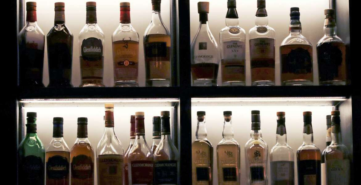 In this Dec. 10, 2019, photo a vast array of fine single malt scotch bottles are displayed at Wink & Nod, basement-dwelling, speakeasy-like bar, in Boston. In this era of bottomless mimosas, craft beers and ever-present happy hours, it's striking to recall that 100 years ago the United States imposed a nationwide ban on the production and sale of all types of alcohol. (AP Photo/Charles Krupa)