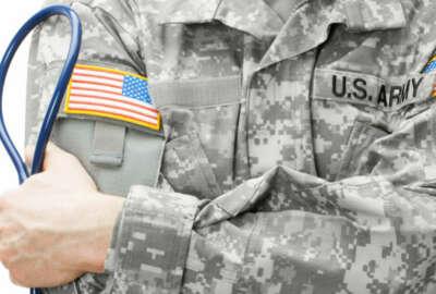 US Army doctor holding stethoscope - studio shot