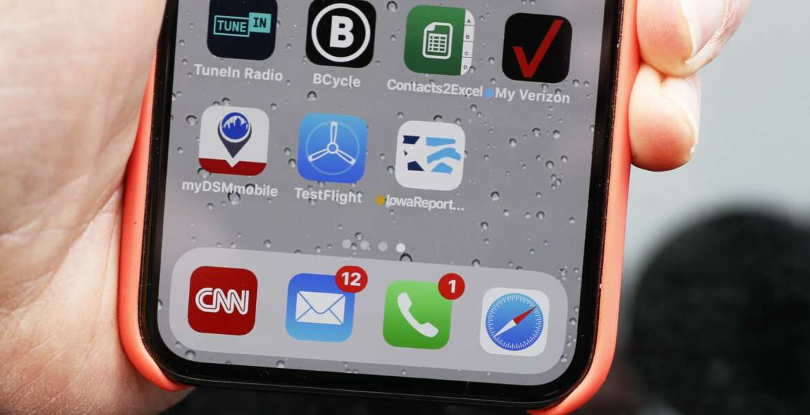 Precinct captain Carl Voss, of Des Moines, Iowa, holds his iPhone that shows the Iowa Democratic Party's caucus reporting app icon Tuesday, Feb. 4, 2020, in Des Moines, Iowa. (AP Photo/Charlie Neibergall)