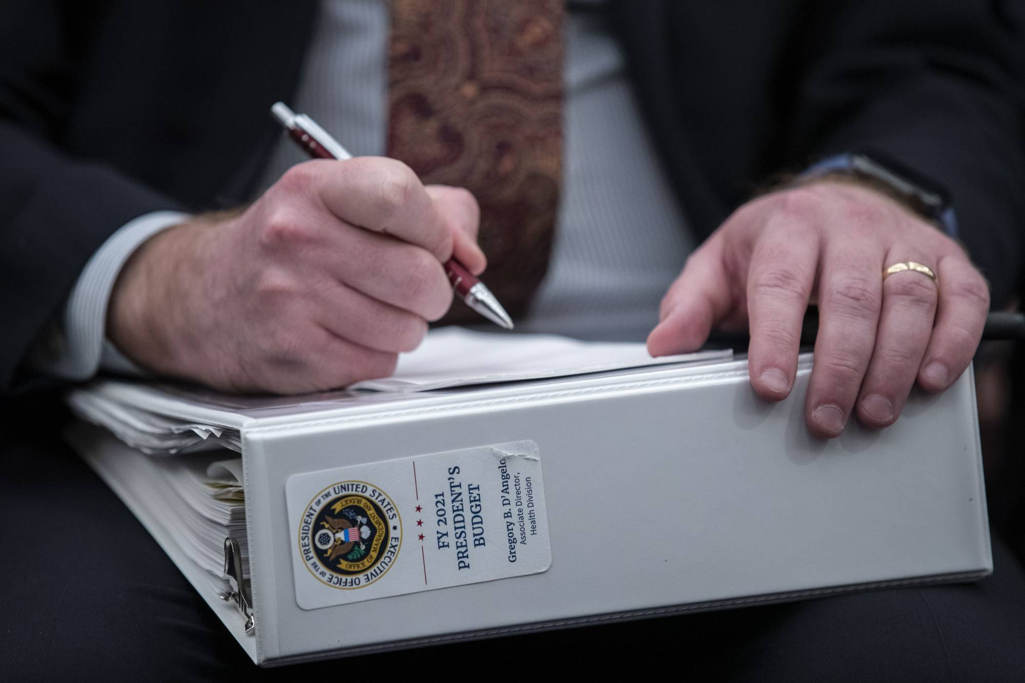 An aide holds a copy of the President's Budget for 2021, as Office of Management and Budget Acting Director Russell Vought testifies during a hearing of the House Budget Committee about President Trump's budget for Fiscal Year 2021, on Capitol Hill, Wednesday, Feb. 12, 2020, in Washington. (AP Photo/Alex Brandon)