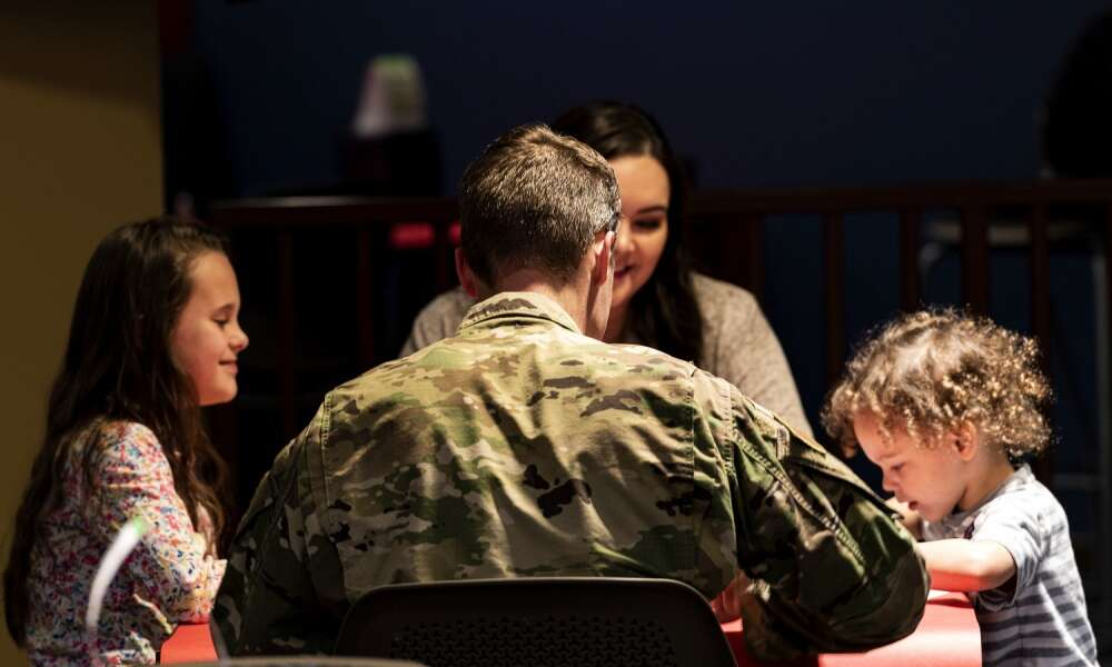 Senior Master Sgt. Paul Kalle, 723d Aircraft Maintenance Squadron first sergeant, speaks with a family during a Deployed Spouses Dinner Feb. 18, 2020, at Moody Air Force Base, Georgia. The monthly event is a free dinner at Georgia Pines Dining Facility designed as a 'thank you' for each families' support and sacrifice while their spouse is deployed or on a remote assignment. The dinner, occurring on every third Tuesday of the month, provides an opportunity for spouses to interact with other families of deployed Airmen, key spouses and unit leadership, as well as provide a break for the spouse while military sponsor is deployed. The next Deployed Spouses Dinner will be March 17. (U.S. Air Force photo by Senior Airman Erick Requadt)