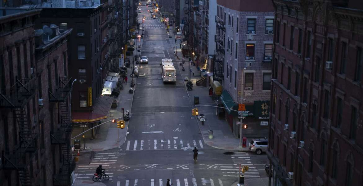 Bicyclists and a pedestrian pass through a quiet Manhattan street, Thursday, March 26, 2020, during the coronavirus pandemic in New York. Because of Gov. Andrew Cuomo's