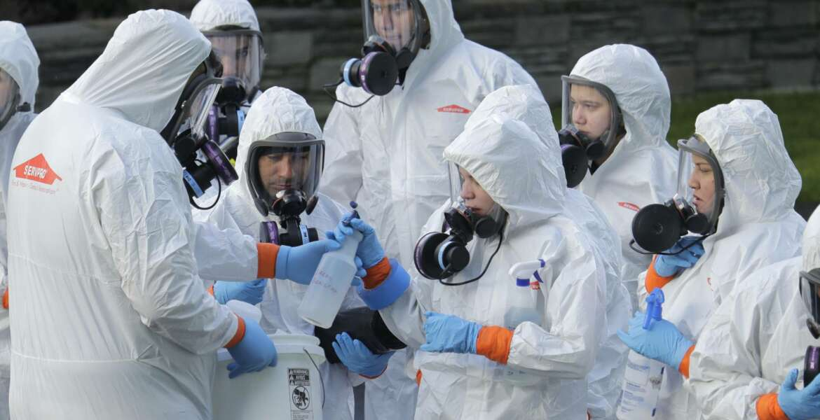 Workers from a Servpro disaster recovery team wearing protective suits and respirators are given supplies as they line up before entering the Life Care Center in Kirkland, Wash., to begin cleaning and disinfecting the facility, Wednesday, March 11, 2020. The nursing home is at the center of the coronavirus outbreak in Washington state. For most people, the virus causes only mild or moderate symptoms. For some it can cause more severe illness, especially in older adults and people with existing health problems. (AP Photo/Ted S. Warren)