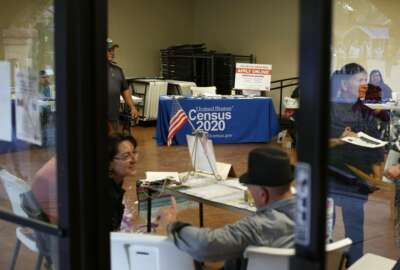 In this Feb. 8, 2020, photo, people volunteer to get people registered to vote and a booth offering employment for the upcoming 2020 census stands in the background, during the celebration of the town's 45th year since it was incorporated, in Guadalupe, Ariz. Today, nearly a third of Guadalupe's 6,500 residents say they are Native American and about 75% of all races identify as Hispanic. A third also struggle with poverty in a community where the median annual household income is around $32,000 and the average owner-occupied home is valued at less than $90,000. (AP Photo/Dario Lopez-MIlls)