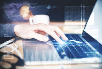 Side view of female hands using laptop with digital business interface on desk with blurry coffee cup and other items. Technology and finance concept. Double exposure