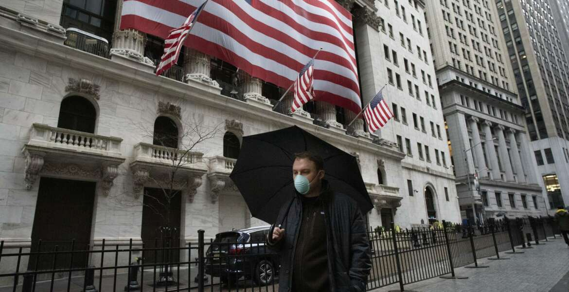 A man wearing a mask walks by the New York Stock Exchange, Tuesday, March 17, 2020. Share prices are volatile after a brutal sell-off that gave the U.S. stock market its worst loss in more than three decades. Markets in Europe lost early gains and were trading lower on Tuesday (AP Photo/Mark Lennihan)
