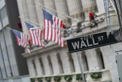 FILE - In this Jan. 3, 2020 file photo, the Wall St. street sign is framed by American flags flying outside the New York Stock Exchange  in New York.  Shares are down in European trading on Friday, March 27,  and expected to drop on Wall Street as investors weigh news of more virus infections against the economic stimulus provided by world authorities.  (AP Photo/Mary Altaffer, File)