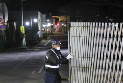 A guard opens the gate to the town in Futaba, Fukushima prefecture, northern Japan at midnight Wednesday, March 4, 2020. Japan's government partially lifted an entry ban for Futaba, the last town that remained off-limits since it was entirely forced to evacuate following the Fukushima nuclear disaster nine years ago.  (Kyodo News via AP)