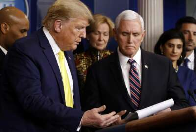President Donald Trump gestures for Vice President Mike Pence to speaks in the briefing room of the White House in Washington, Monday, March 9, 2020, about the coronavirus outbreak. (AP Photo/Patrick Semansky)