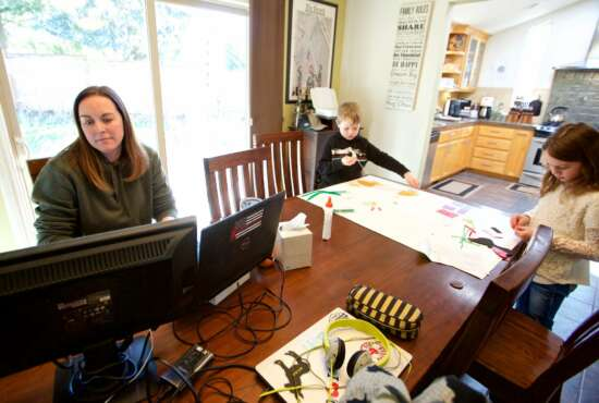 In this Tuesday, March 17, 2020 photo Kim Borton, left, works from home while her children Logan Borton, center, age 6 and Katie Borton, age 7, as they work on an art project in Beaverton, Ore. Borton works for Columbia Sportswear in supply chain account operations. Her children attend Hiteon Elementary school and have sent home some home work packets and emails with links for remote learning, but she has also added her own curriculum to their day to fill the voids so she can continue to work and keep the kids busy. (AP Photo/Craig Mitchelldyer)