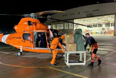 In this Friday, March 6, 2020, image provided by the U.S. Coast Guard, Air Station crew members load personal protective equipment into a helicopter in San Francisco. Thousands of anxious people were confined Saturday to a cruise ship circling in international waters off the San Francisco Bay Area, after 21 passengers and crew members tested positive for the new coronavirus. The Grand Princess was forbidden to dock in San Francisco amid evidence that the vessel had been the breeding ground for a cluster of nearly 20 cases that resulted in at least one death after its previous voyage. (Petty Officer 3rd Class Taylor Bacon/U.S. Coast Guard District 11 via AP)