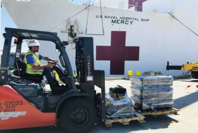 Steve King, a Naval Facilities Engineering Command Southwest forklift driver, prepares to deliver pallets during a supply load aboard the Military Sealift Command hospital ship USNS Mercy (T-AH 19) at Naval Base San Diego, adjacent to San Diego, Calif., Saturday, March 21, 2020. Mercy is preparing to deploy in support of the nation's COVID-19 response efforts and will serve as a referral hospital for non-COVID-19 patients currently admitted to shore-based hospitals. (Senior Chief Mass Communication Specialist Mike Jones/U.S. Navy via AP)