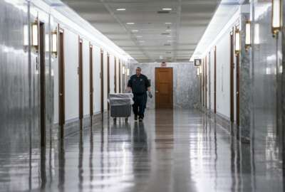 A workman walks through the empty corridors of the Dirksen Senate Office Building on Capitol Hill as lawmakers negotiate on the emergency coronavirus response legislation, in Washington, Wednesday, March 18, 2020. (AP Photo/J. Scott Applewhite)