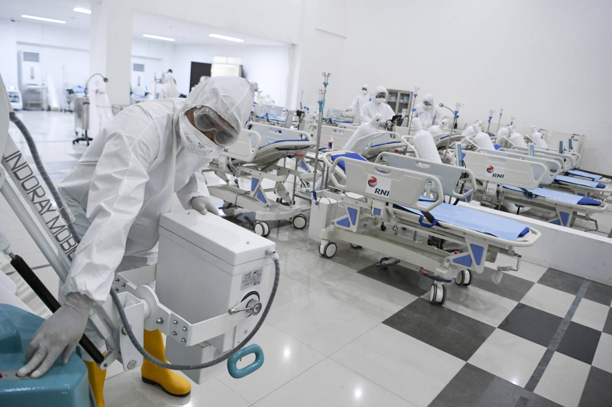 Staff inspect medical equipments at an emergency hospital set up amid the new coronavirus outbreak in Jakarta, Indonesia, Monday, March 23, 2020. Indonesia has changed towers built to house athletes in the 2018 Asian Games to emergency hospitals with a 3,000-bed capacity in the country's hard-hit capital, where new patients have surged in the past week. (Hafidz Mubarak A/Pool Photo via AP)