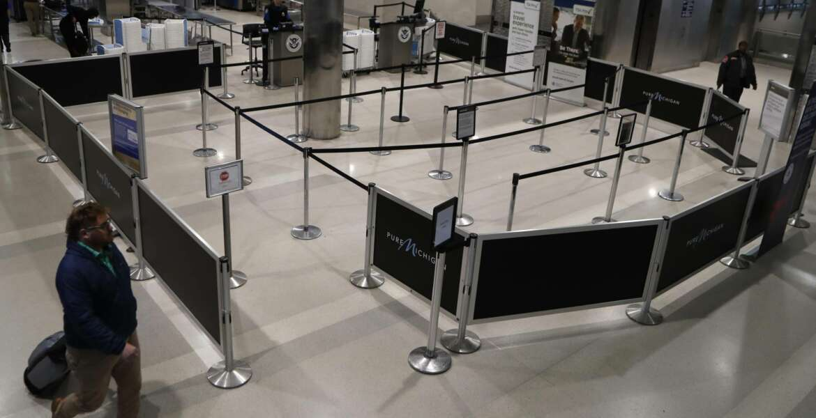 An airline passenger walks by the vacant TSA checkin at the Detroit Metropolitan Airport, Monday, March 23, 2020, in Romulus, Mich. The COVID-19 coronavirus has considerably slowed air travel. (AP Photo/Carlos Osorio)