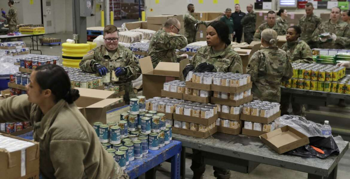 FILE - In this March 24, 2020, file photo, members of The Ohio National Guard assist in repackaging emergency food boxes for food distribution at the Cleveland Food Bank in Cleveland. The use of National Guard units around the country to help with the response to the coronavirus pandemic is prompting rumors of a national lockdown or even martial law. Guard units are now helping to transport medical supplies, distribute food and even help direct traffic at drive-through testing sites. (AP Photo/Tony Dejak, File)