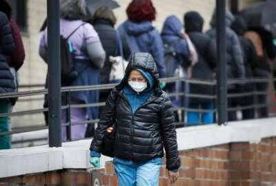 A medical worker wearing a single protective glove and a face mask walks past a line of workers and visitors waiting to be tested for COVID-19, the disease caused by the new coronavirus, at the main entrance to the Department of Veterans Affairs Medical Center, Monday, March 23, 2020, in New York.  (AP Photo/John Minchillo)