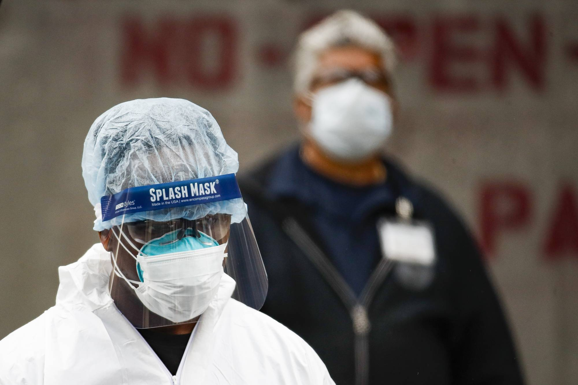 Medical workers wearing personal protective equipment due to COVID-19 concerns pause for rest before loading bodies into a refrigerated container truck functioning as a makeshift morgue, Tuesday, March 31, 2020, at Brooklyn Hospital Center in Brooklyn borough of New York. The new coronavirus causes mild or moderate symptoms for most people, but for some, especially older adults and people with existing health problems, it can cause more severe illness or death. (AP Photo/John Minchillo)