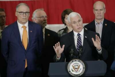 Vice President Mike Pence, at podium, speaks as Gov. Jay Inslee, left, and other officials look on during a news conference, Thursday, March 5, 2020, at Camp Murray in Washington state. Pence was in Washington to discuss the state's efforts to fight the spread of the COVID-19 coronavirus. (AP Photo/Ted S. Warren)