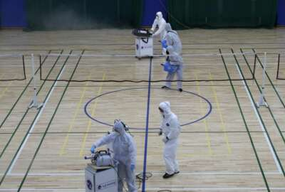 In this Feb. 25, 2020, file photo, workers in protective suits spray disinfectant as a precaution against the COVID-19 at an indoor gymnasium in Seoul, South Korea. As the coronavirus spreads around the world, many events that normally would draw large numbers of people are being canceled or played without fans. (AP Photo/Lee Jin-man, File)