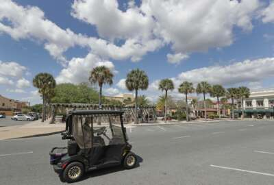 In this Thursday, March 19, 2020 photo, a resident drives his golf cart down what usually is a busy street by the Spanish Springs town square in The Villages, Fla. Three town squares in the community are closed due to the coronavirus through the end of the month in what is perhaps the largest concentration of seniors in the U.S. (AP Photo/John Raoux)