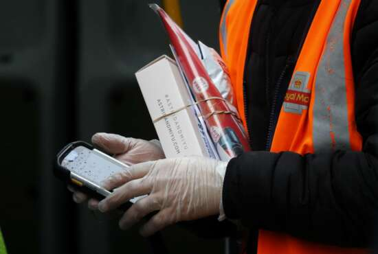 In this March 5, 2020, photo, a Royal Mail employee wears gloves as he hold parcels and the signature handheld as he delivers in London. While white collar workers trying to avoid contagion can work from home or call in sick if they experience symptoms of the new virus, such precautions are not an options for the millions of waiters, delivery workers, cashiers, ride-hailing drivers, museum attendants and countless others who routinely come into contact with the public. (AP Photo/Frank Augstein)