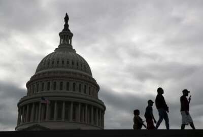 Visitors walk past the U.S. Capitol dome on Capitol Hill in Washington, Thursday, March 12, 2020. Congress is shutting the Capitol and all House and Senate office buildings to the public until April in reaction to the spread of the coronavirus outbreak. (AP Photo/Patrick Semansky)