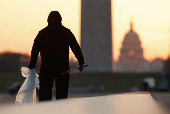 A National Park Service worker picks up trash along the drained Lincoln Memorial Reflecting Pool as the Washington Monument and the U.S. Capitol are seen in the distance in Washington, at sunrise Wednesday, March 18, 2020. The number of tourist is down ahead of an expected surge in coronavirus cases. (AP Photo/Carolyn Kaster)