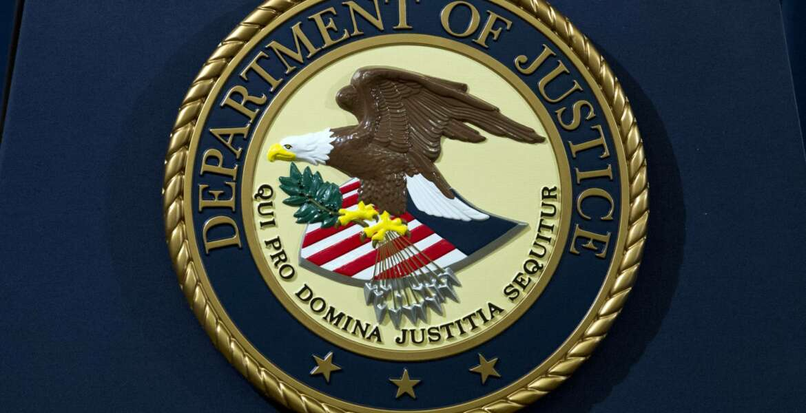 FILE - In this Nov. 28, 2018, file photo, the Department of Justice seal is seen in Washington, D.C. An internet firm is ending the automated registration of website names that include words or phrases related to the COVID-19 pandemic, in an attempt to combat coronavirus-related fraud. Los Angeles-based Namecheap Inc. made the pledge after a federal judge in Texas on Sunday, March 22, 2020, ordered the takedown of a website the U.S. Department of Justice accused of stealing credit card information while offering fake coronavirus vaccine kits. (AP Photo/Jose Luis Magana, File)