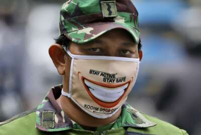 An Indonesian soldier wears face mask as he and his team man a checkpoint during the large-scale restriction imposed by the local government to curb the spread of the coronavirus outbreak in Jakarta, Indonesia, Wednesday, April 15, 2020. Indonesia's capital kicked off the stricter restriction last week as the metropolitan area has become Indonesia's coronavirus epicenter. (AP Photo/Dita Alangkara)