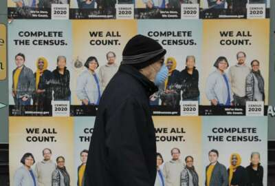 A man wearing a mask walks past posters encouraging participation in the 2020 Census, Wednesday, April 1, 2020, in Seattle's Capitol Hill neighborhood. Wednesday is Census Day, the date used to reference where a person lives for the once-a-decade count, as the U.S. is almost paralyzed by the spread of the novel coronavirus, but census officials vowed the job would be completed by its year-end deadline. (AP Photo/Ted S. Warren)