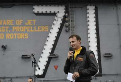 In this Nov. 15, 2029, photo U.S. Navy Capt. Brett Crozier, commanding officer of the aircraft carrier USS Theodore Roosevelt (CVN 71), addresses the crew during an all-hands call on the ship's flight deck while conducting routine operations in the Eastern Pacific Ocean. U.S. defense leaders are backing the Navy's decision to fire the ship captain who sought help for his coronavirus-stricken aircraft carrier, even as videos showed his sailors cheering him as he walked off the vessel. Videos went viral on social media Friday, April 3, 2020, showing hundreds of sailors gathered on the ship chanting and applauding Navy Capt. Brett Crozier as he walked down the ramp, turned, saluted, waved and got into a waiting car. (U.S. Navy Photo by Mass Communication Specialist 3rd Class Nicholas Huynh via AP)
