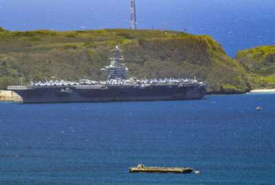 The USS Theodore Roosevelt, a Nimitz-class nuclear powered aircraft carrier, is docked along Kilo Wharf of Naval Base Guam in Sumay,  Friday, April 3, 2020. The aircraft carrier, with a crew of nearly 5,000, is docked in Guam, and the Navy has said as many as 3,000 will be taken off the ship and quarantined by Friday. More than 100 sailors on the ship have tested positive for the virus, but none is hospitalized.  (Rick Cruz/The Pacific Daily via AP)
