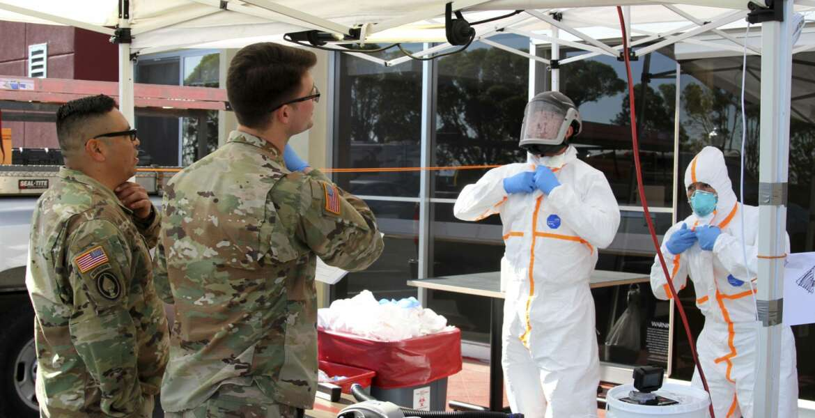 This March 27, 2020 photo provided by the California Army National Guard shows Sgt. Jose A. Magana, left, and Pfc. Michael Daggi of the California National Guard's Medical Detachment instructing California Emergency Medical Service Authority (EMSA) staff members on properly removing personal protective equipment at a San Mateo County COVID-19 treatment facility in Burlingame, Calif. Cal Guard's medical teams are actively assisting local and state agencies contain the coronavirus epidemic. This treatment facility houses patients who tested positive for COVID-19. (Staff Sgt. Eddie Siguenza/Army National Guard via AP))