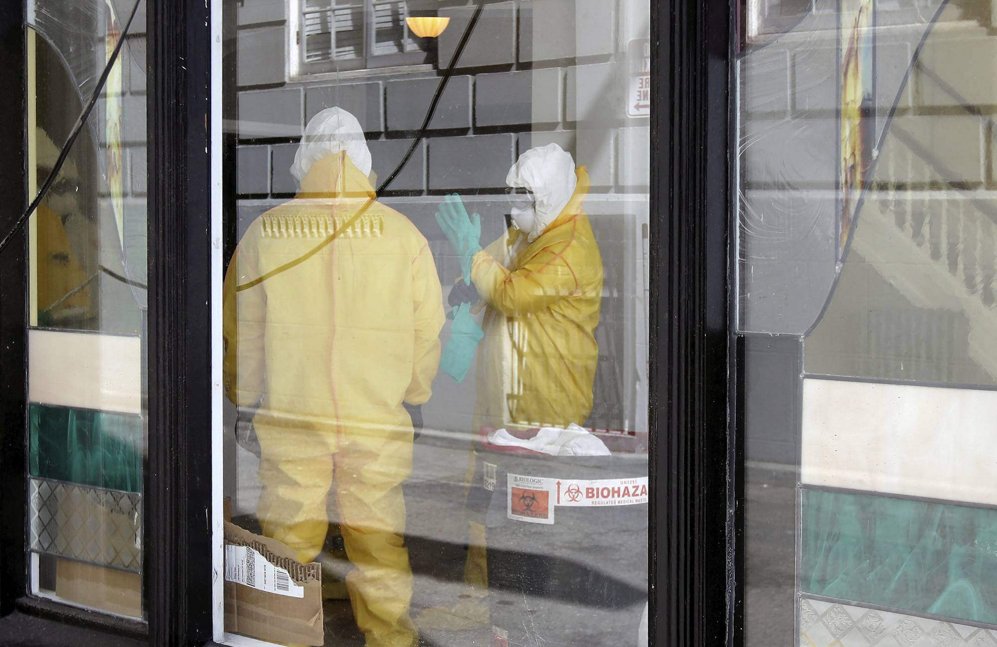 FILE - In this Thursday, April 2, 2020, file photo, workers in hazardous material suits clean inside the Abigail Hotel in San Francisco. The hotel is one of several private hotels San Francisco has contracted with to take vulnerable people who show symptoms or are awaiting test results for the coronavirus. Gov. Gavin Newsom, who made solving the state's homelessness crisis a priority even before the pandemic struck, announced in mid-March his administration was negotiating with 900 hotels to house the homeless. Two weeks ago he announced Project Roomkey, a program in which the Federal Emergency Management Agency will pay 75% of costs associated with housing some homeless, including people who test positive or may have been exposed to the virus, and older homeless people and those with underlying health conditions. (AP Photo/Jeff Chiu, File)