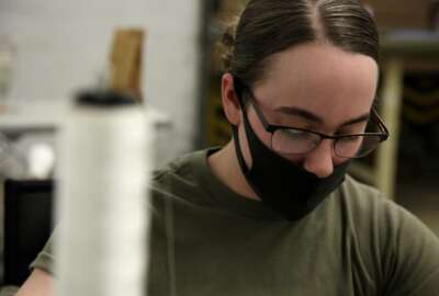 In this April 17, 2020 photo, a mask covers the face of a U.S. Army Fort Bragg soldier as she sews PPE. Her unit has already constructed thousands of masks since