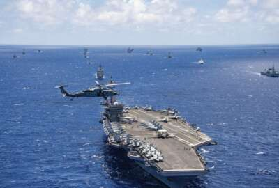 FILE -- In this July 26, 2018, file photo provided by the U.S. Navy, the aircraft carrier USS Carl Vinson participates in a group sail during the Rim of the Pacific exercise off the coast of Hawaii. Hawaii's governor says he will ask the U.S. military to postpone the world's largest maritime exercises because of the coronavirus pandemic. (Petty Officer 1st Class Arthurgwain L. Marquez/U.S. Navy via AP, File)