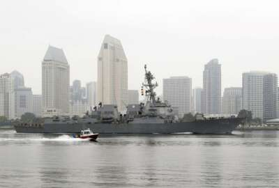 The USS Kidd passes downtown San Diego as it returns to Naval Base San Diego, Tuesday, April 28, 2020, seen from Coronado, Calif. As the American destroyer heads home with an outbreak in cases of COVID-19, relatives and friends of the 350 crew members prayed for their health while Navy officials vowed to keep the outbreak, the second to strike a Navy vessel at sea, from spreading. (AP Photo/Gregory Bull)