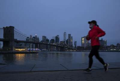 A jogger wearing a mask runs along Brooklyn Bridge Park, Tuesday night, April 14, 2020 during the coronavirus pandemic in New York. Known as
